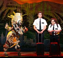 "Phyre Hawkins, left, dons a ""Lion King"" costume to help prepare two Mormon missionaries (Gavin Creel and Jared Gertner) before they embark to Uganda in ""The Book of Mormon"" at the Curran Theatre. (Photo: Joan Marcus)"
