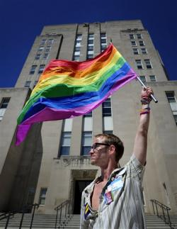 Gary Jones, 37, Racine, holds aloft the rainbow striped gay and lesbian pride flag in front of the Racine County Courthouse