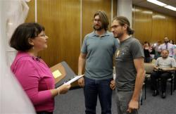 Jake Miller, right, 30, and Craig Bowen, 35, are married by Marion County Clerk Beth White, left, in Indianapolis.