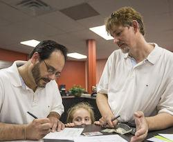 Greg Bovo, left, and his partner David Schmokel fill out a marriage license application as their adopted daughter, Sophia Bovo-Schmokel, 5, looks on