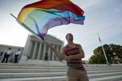 Gay rights advocate Vin Testa waves a rainbow flag in front of the U.S. Supreme Court.