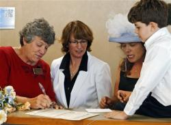Denver County Clerk Debra Johnson, left, signs the marriage license of Fran Simon and Anna Simon as their son Jeremy watches.