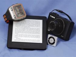 A Garmin Forerunner 310XT GPS Sports Running Multisports Speed & Distance Watch, an Amazon Kindle, Apple iPod Shuffle and a Canon S110 camera.