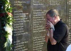 Chris Rhoads, who was the General Manager of Flight Attendants for TWA, reacts at the memorial wall during the 20th anniversary of the TWA Flight 800 plane crash at Smith Point County Park.