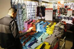 """In this Thursday, March 10, 2016, file photo, a man looks at shirts and neckties that are part of a """"Buy One Get One for a Penny"""" sale at a J.C. Penney store"""