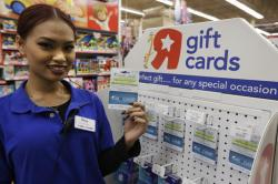 Toys R Us employee Davy Pen holds a Gift of College gift card.