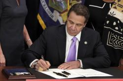 In this April 4, 2016 file photo, New York Gov. Andrew Cuomo signs a law that will gradually raise New York's minimum wage to $15, at the Javits Convention Center, in New York. New York joins 18 other states by raising its minimum wage in 2017
