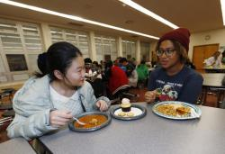 In this Jan. 27, 2017 photo, foreign exchange student Miaofan Chen, left, of Hefei, China, chats with Thandi Glick during a potluck meal for Chinese exchange students and their families at a school in Denver.
