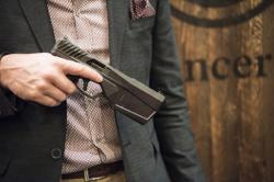 In this photo taken Jan. 17, 2017, Josh Waldron, co-founder and CEO of SilencerCo, holds one of his company's Maxim 9 products, holds a 9mm handgun, in Las Vegas, in which the suppressor is embedded into the barrel