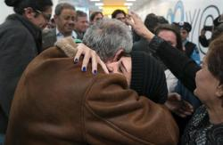 In a Monday, Feb. 6, 2017 file photo, family members who have just arrived from Syria embrace and are greeted by family who live in the United States upon their arrival at John F. Kennedy International Airport in New York.
