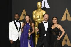 "Joanna Natasegara, second from left, and Orlando von Einsiedel, winners of the award for for best documentary short subject for ""The White Helmets"", pose in the press room with David Oyelowo, left, and Salma Hayek, right."