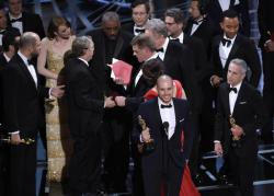 "Fred Berger, producer of ""La La Land,"" foreground center, gives his acceptance speech as members of PricewaterhouseCoopers, Brian Cullinan, holding red envelope, and Martha L. Ruiz, in red dress, and a stage manager discuss the best picture announcement error among the cast at the Oscars."