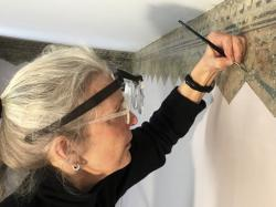Art restoration expert Margaret Saliske works on hand-painted borders at the home of artist Thomas Cole, in Catskill, N.Y.