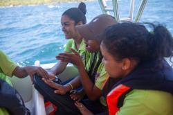 In this Tuesday, March 14, 2017 photo, hearing impaired student Katherine Arias, center, places her hand on a Subpac backpack to feel the melodies of previously recorded whale sounds as she describes the vibrations with her hands, during a whale watching tour near Samana, Dominican Republic