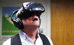In this Jan. 26, 2017, photo, Joseph Nugent, a Boston College English professor, wears virtual reality goggles at the school's virtual reality lab in Boston