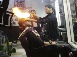 Palestinian hair dresser Ramadan Adwan uses fire to straighten the hair of a costumer in his barber shop in the Rafah refugee camp in the Gaza Strip.