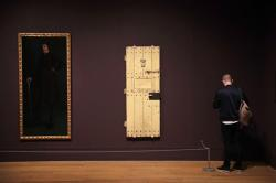 """A man stands next to American artist Robert Harper Pennington's """"Oscar Wild"""" painting and the door of Oscar Wilde's prison cell at Reading Jail, during a media preview for the """"Queer British Art 1861-1967"""" exhibition at Tate Britain."""