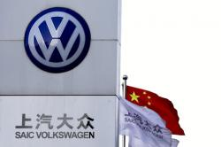 A Chinese national flag flutters near a SAIC Volkswagen, a joint venture between SAIC Motor and Volkswagen's dealer showroom and service center in Beijing, Tuesday, April 18, 2017