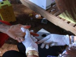 A Cambodian health agent pricks the finger of a woman who sought an HIV blood test