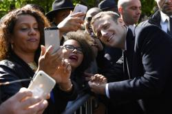 President-elect Emmanuel Macron, right, poses for a picture with supporters after a ceremony to mark the anniversary of the abolition of slavery, Wednesday May 10, 2017 in Paris