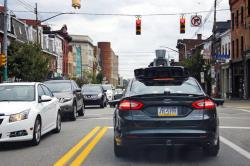 In this Wednesday, Sept. 14, 2016, file photo, a self-driving Uber car stops at a red light on Liberty Avenue through the Bloomfield neighborhood of Pittsburgh