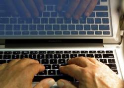 In this Feb. 27, 2013, file photo, hands type on a computer keyboard in Los Angeles