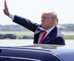 President Donald Trump waves from his car after speaking during a stop at General Mitchell International Airport Tuesday, June 13, 2017, in Milwaukee