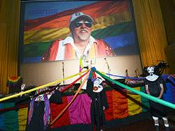 Sister Timothy Simplicity, on stage, reads a proclamation designating Gilbert Baker as Sister Betsy Ross of the Sisters of Perpetual Indulgence, while other Sisters hold rainbow ribbons strung down the aisles of the Castro Theatre to open the celebration of life for Baker, the creator of the rainbow flag
