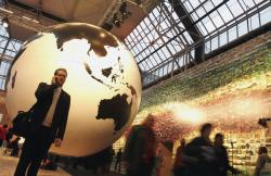 In this Tuesday Dec. 15, 2009 file photo, a man speaks on his cell phone in front of a giant globe in Copenhagen