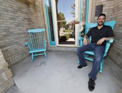 In this Wednesday, June 14, 2017, photograph, Danny Aguilar takes a seat in one of the rocking chair on the front porch of his home in Lakewood, Colo.
