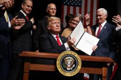 President Donald Trump shows a signed executive order on Cuba policy.