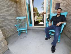 Danny Aguilar takes a seat in one of the rocking chair on the front porch of his home in Lakewood, Colo.