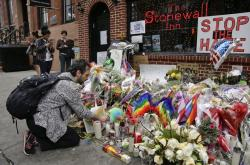 A man lights candles on a memorial outside the Stonewall Inn for victims of the Orlando Shooting, in New York.
