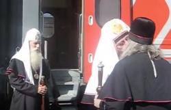 Metropolitan Kornily (left) looks on as two church officials kiss