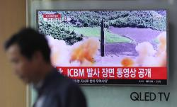 A man walks by a TV screen showing a local news program reporting about North Korea's missile firing at Seoul Train Station in Seoul, South Korea, Wednesday, July 5, 2017