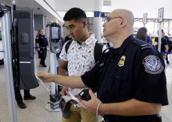 In a June 29, 2017, photo, U.S. Customs and Border Protection Officer Sanan Jackson, right, helps a passenger navigate the new face recognition kiosks at gate E7 for a United Airlines flight to Tokyo at Bush Intercontinental Airport in Houston