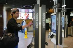 Brandon Alba from Milwaukee, orders food at a self-service kiosk at a McDonald's restaurant in Chicago.