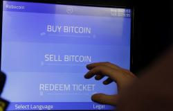 In this Thursday, March 20, 2014, file photo, Christopher David uses a Robocoin kiosk to sell bitcoins outside of the 500 Startups' Bitcoinferance in Mountain View, Calif.