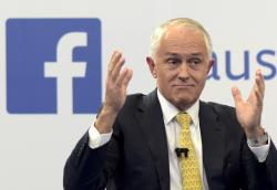 In this June 17, 2016 file photo, Australian Prime Minister Malcolm Turnbull raises his hands as he speaks during a leaders debate hosted by Facebook Australia and News.com.au in Sydney
