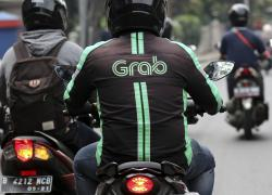A GrabBike driver rides on his motorbike in Jakarta, Indonesia, Monday, July 24, 2017