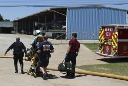 In this April 29, 2014, photo provided by the Bryan, Texas, Fire Department, firefighters transport an injured worker in a stretcher to the ambulance