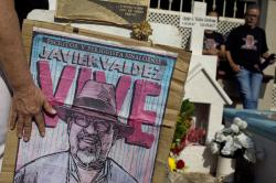 In this July 1, 2017 photo, relatives of slain journalist Javier Valdez, co-founder of Riodoce, stand at a memorial set up at the spot where he was murdered in Culiacan, Sinaloa state, Mexico