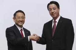 Toyota Motor Corp. President Akio Toyoda, left, and Mazda Motor Corp. President Masamichi Kogai, right, pose for media prior to a press conference in Tokyo Friday, Aug. 4, 2017