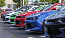 In this Wednesday, April 26, 2017, photo, Chevrolet Camaros are lined up in the lot of a Chevrolet dealership in Richmond, Va.