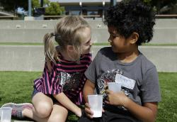In this Tuesday, July 11, 2017 photo, campers Gracie, left, leans toward Nugget during an activity at the Bay Area Rainbow Day Camp in El Cerrito, Calif.