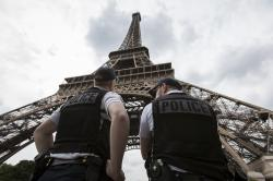 French riot police officers patrol under the Eiffel Tower, in Paris.