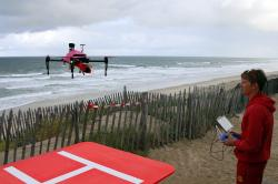 Lifeguard Geoffrey Leventec pilots a rescue drone from the beach of Biscarrosse, southwestern France, Tuesday, Aug. 8, 2017.