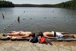 Swimmers lie on the edge of Walden Pond in Concord, Mass.