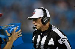 In this Wednesday, Aug. 9, 2017 photo, referee Tony Corrente (99) looks at the instant replay on a Microsoft Surface tablet during the second half of an NFL preseason football game between the Carolina Panthers and the Houston Texans in Charlotte, N.C.