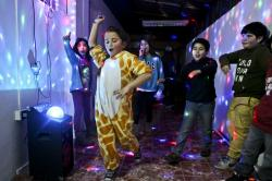 Selenna, sporting a giraffe costume for the fun of it, dances with other kids at the end of a gender identity workshop at a community center in Santiago, Chile.